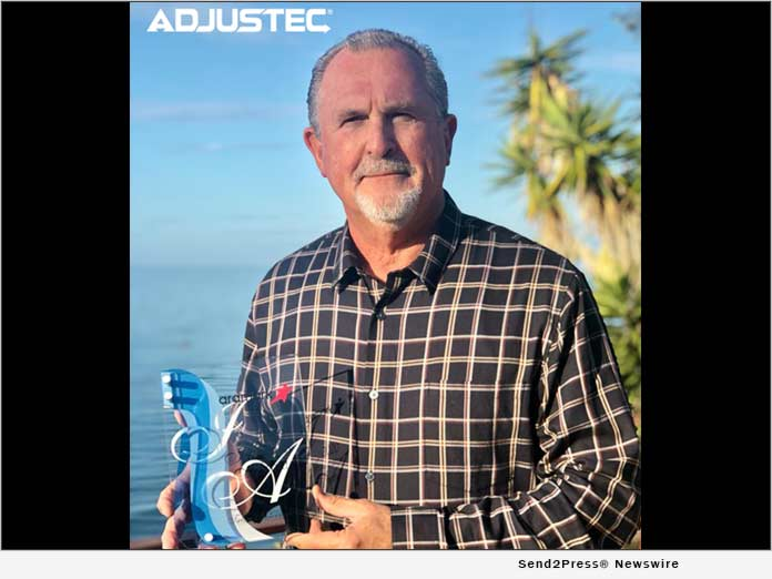 Herman Roup, President of Adjustec, Holding the Aramark 2020 Innovator Award